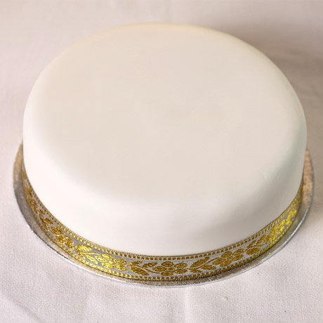 A single tier plain white decorated cake on glass stand